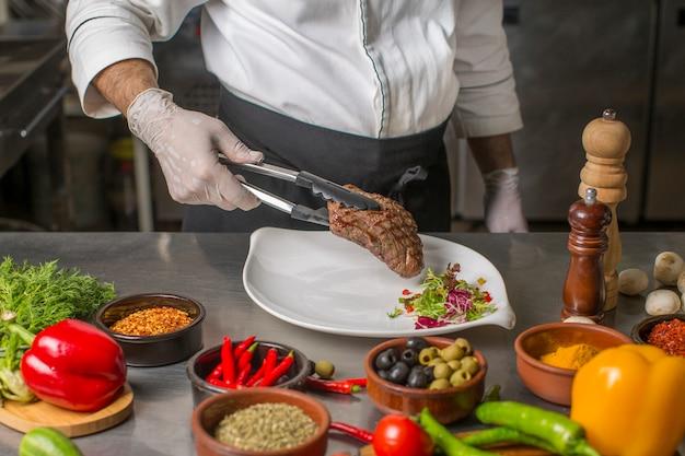Cuoco unico che mette bistecca alla griglia al piatto di servizio con insalata di erbe