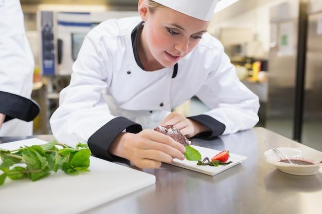 Chef putting mint on dessert plate