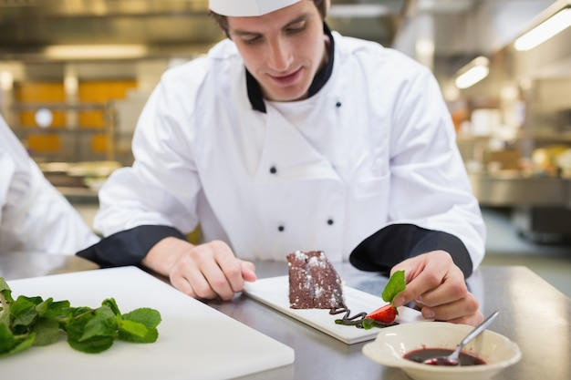 Chef putting mint leaf with his dessert