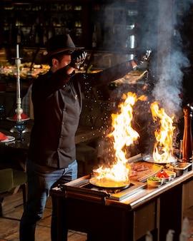 油で2つの燃える鍋に塩を入れてシェフ