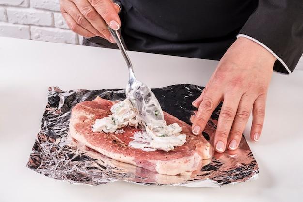 Шеф-повар ставит соус из верхней части мяса