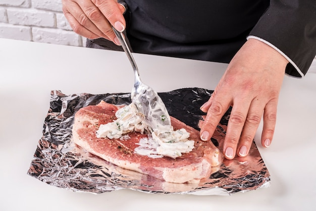 Chef putting sauce of top of meat