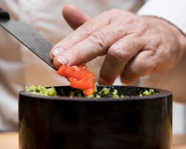 Cuoco unico che mette i pomodori sopra l'avocado
