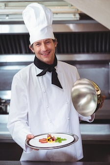 Chef raising a bell of a dish