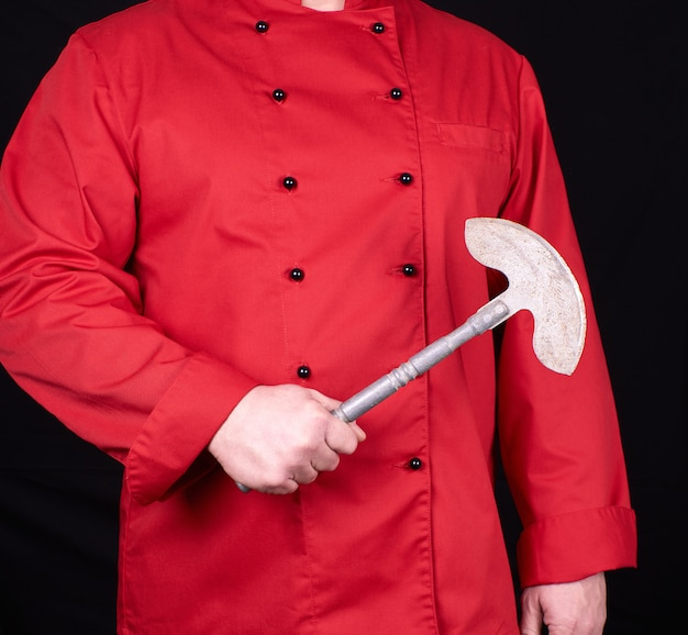 Chef in red uniform holding an old metal knife for meat and vegetables