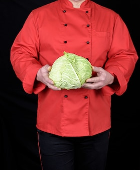 Chef in a red uniform holds a whole cabbage