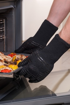 Chef removes the hot tray from the oven in protective gloves