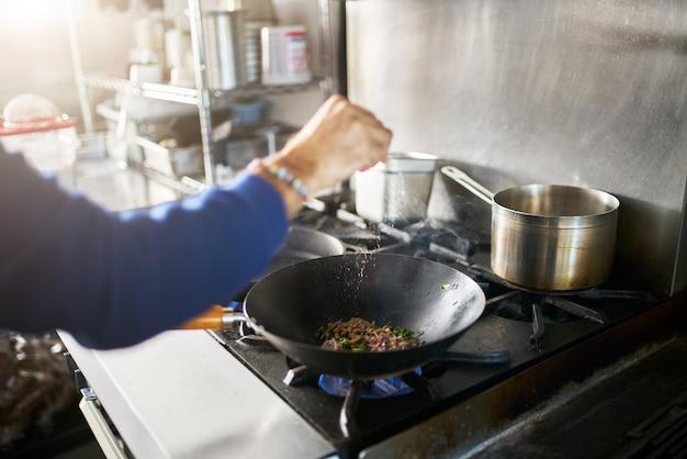 Chef in restaurant kitchen seasoning food in hot skillet wok