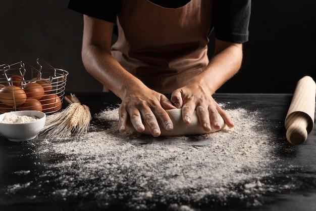Шеф-повар раскатывает тесто в столе