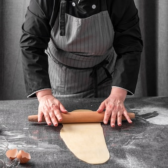 Chef rolling dough on table