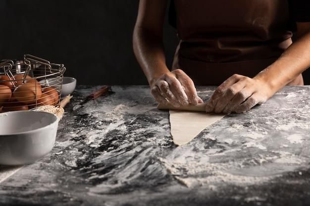 Cuoco unico che rotola il triangolo della pasta per croissant