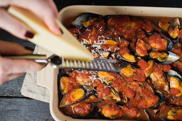 Chef rubs cheese on the mussels in tomato sauce.