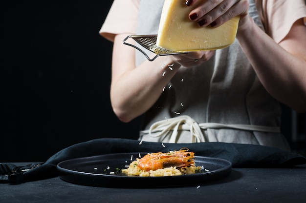 Chef rubs parmesan on italian risotto with shrimp on a black plate.