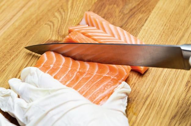 Руки повара крупным планом. на деревянной разделочной доске повар режет ножом красную рыбу. лосось для японских суши