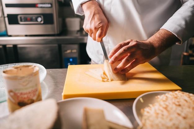 Деталь рук шеф-повара во время нарезки сыра на деревянной разделочной доске