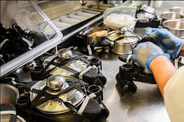 Chef's hands packing food to the pots in automatic restaurant