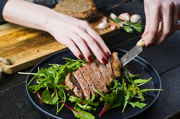 The chef's hands prepare a salad with beef tenderloin and arugula.