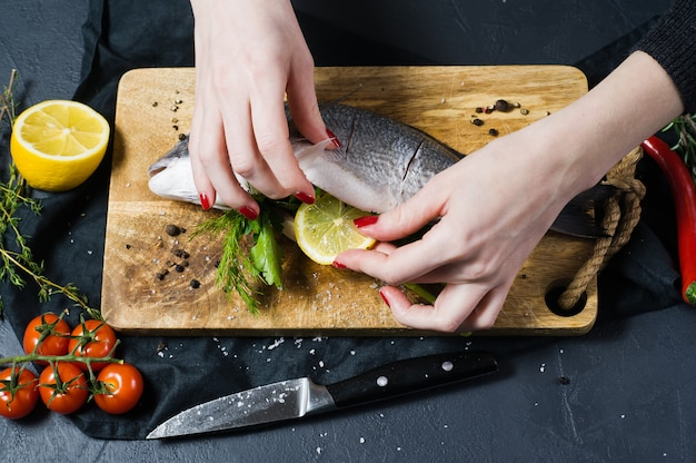 The chef's hands stuffed dorado fish on a wooden chopping board with parsley and cilantro.