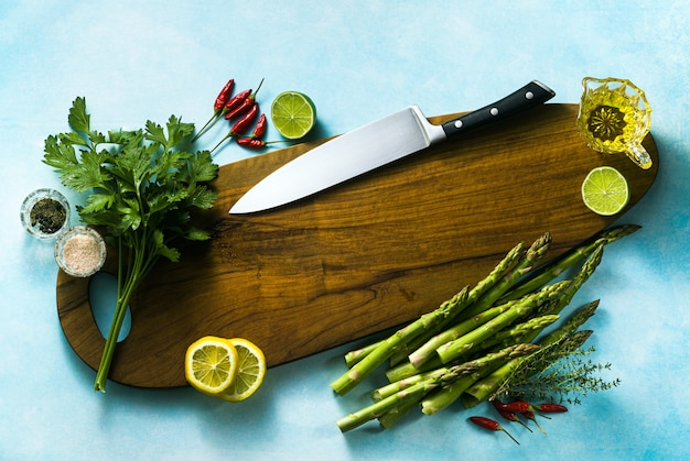 Chef's knife on a cutting board with aromatic herbs and vegetables. food background.