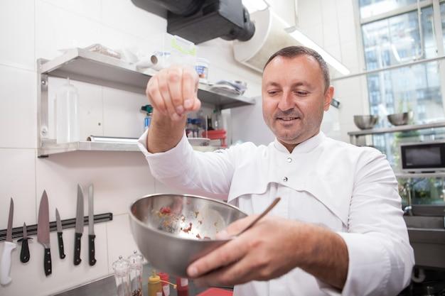 Шеф-повар солит тартар из говядины в металлической миске, работая на кухне ресторана