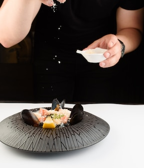 The chef salts a beautiful dish of mussels and seafood on a black plate.