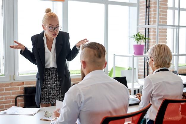 Повар ругает сотрудников за плохой результат на работе, женщина-начальник недовольна работой двух рабочих