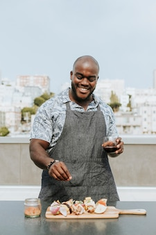 Chef seasoning barbeque skewers at a rooftop party