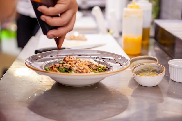 鶏胸肉のサラダを味付けするシェフ。おいしい料理を作る
