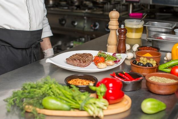 シェフが提供するビーフステーキキノコ、ルッコラのサラダ、トマト