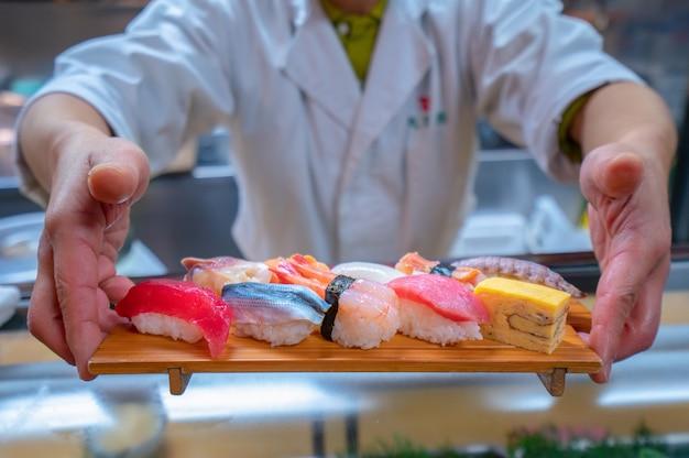 요리사는 손으로 나무 접시에 일본 스시를 제공