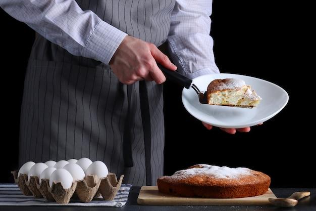 Шеф-повар подает пирог на темном фоне