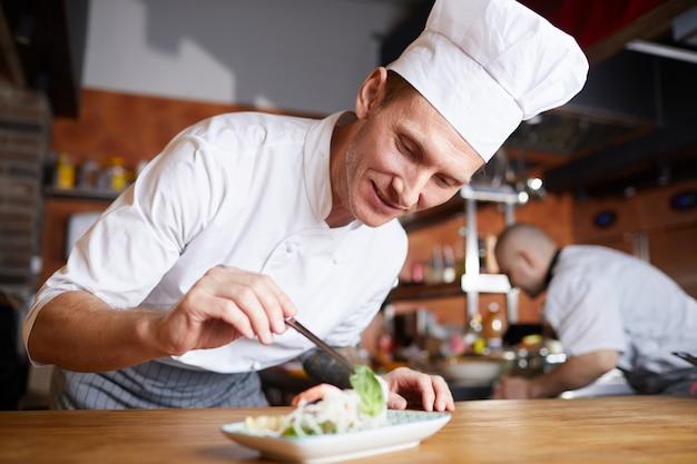 Шеф-повар подает красивое азиатское блюдо