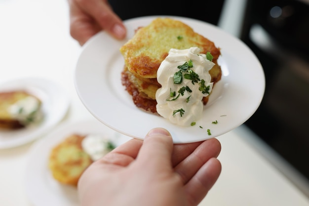 Шеф-повар, подающий белую тарелку с картофельными оладьями и сметаной крупным планом, традиционные белорусские