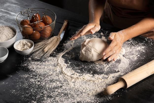 Шеф-повар формирует тесто на столе