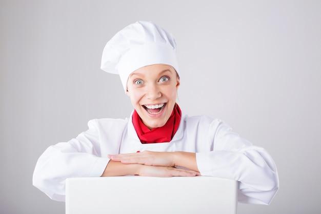 シェフのサイン。紙看板看板を見ている女性のパン屋。白い背景に分離された驚きと面白い表現の女性。