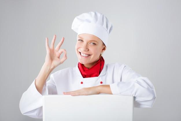 Знак шеф-повара. женщина повар / пекарь, глядя на бумаге знак billboard. удивленная и смешная женщина выражения изолированная на белой стене.