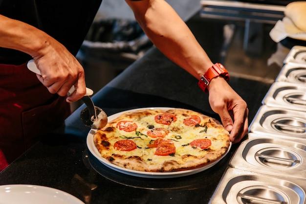 Шеф-повар нарезает горячую пиццу caprese bianca перед подачей на стол. ингредиенты моцарелла