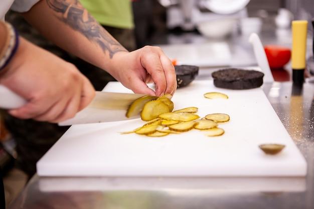 シェフがレストランでおいしいハンバーガーを作るためにピクルスをスライスします。食品の調理
