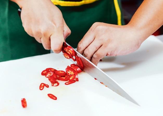 シェフはキッチンで野菜をスライスし、シェフは料理をし、シェフは料理を準備します