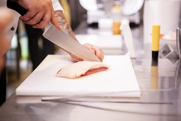 Шеф-повар, нарезавший утиную грудку в кухне ресторана. приготовление мяса