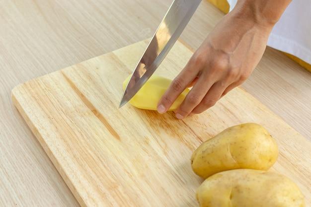 Шеф-повар нарезал свежий картофель на разделочной доске