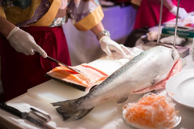 생선회를 위해 신선한 연어를 자르는 요리사