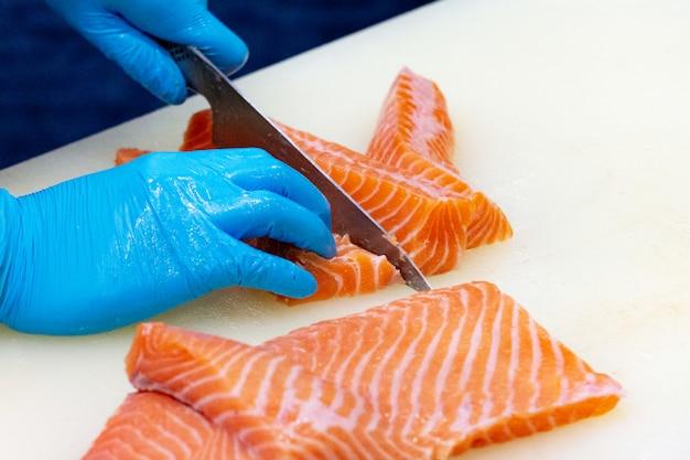 Chef slicing raw fresh salmon, chef preparing a fresh salmon on a cutting board
