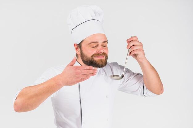Шеф-повар пахнущий блюдо в ковше