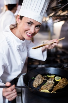 Chef smelling fried fish in the kitchen