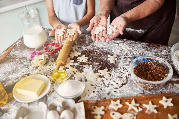 Chef and sous-chef making gingerbread men out of dough