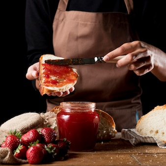 Chef spreading strawberry jam on bred