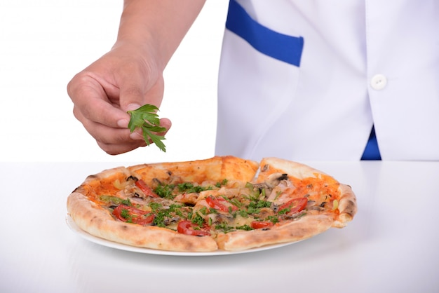 Chef sprinkles pizza with greens