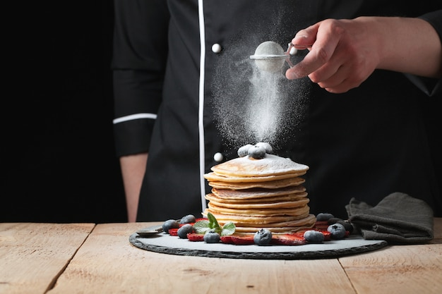 The chef sprinkles powdered sugar on the pancakes.