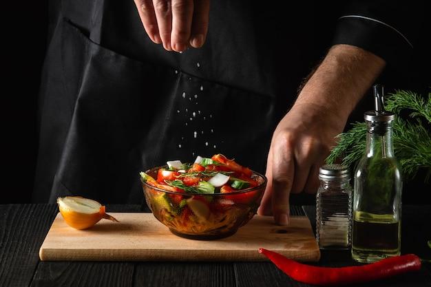 Шеф-повар посыпает салат из соленых свежих овощей в тарелке на деревянном столе